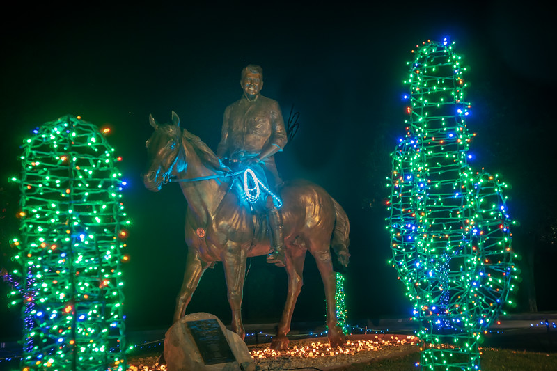 "Equestrian statue of Ronald Reagan alongside Christmas ""cactus"" trees.  A path of golden lights marks his trail."