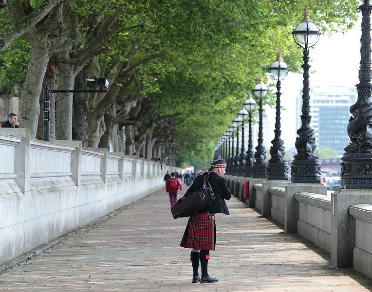 """A piper on his way to work pauses along The River Thames to enjoy the view while collecting his thoughts. Moments later he checked """"Big Ben"""" for the time, then picked up his pace as he hurried along his way.<br /> <br /> Image by Martin McKenzie ~ All Rights Reserved"""