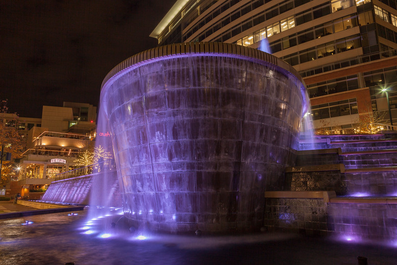 Colored lights display at the Waterwall and fountain by the Woodlands Waterway.