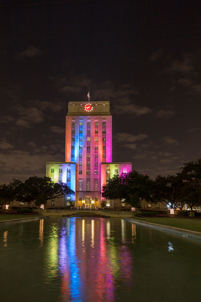 Houston City Hall With Rainbow Of Colored Lights Repeating Varying Patterns  Continuously At Night. Reflecting