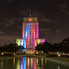 Houston City Hall with rainbow of colored lights repeating varying patterns continuously at night. Reflecting pond adds to the scene.