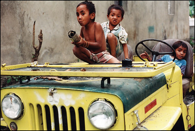 Boys playing in abandoned jeep, Dili.