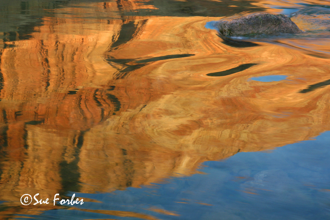 Reflections<br /> Still water of the Colorado River allowed the reflection of the sun on the rock wall of the Grand Canyon