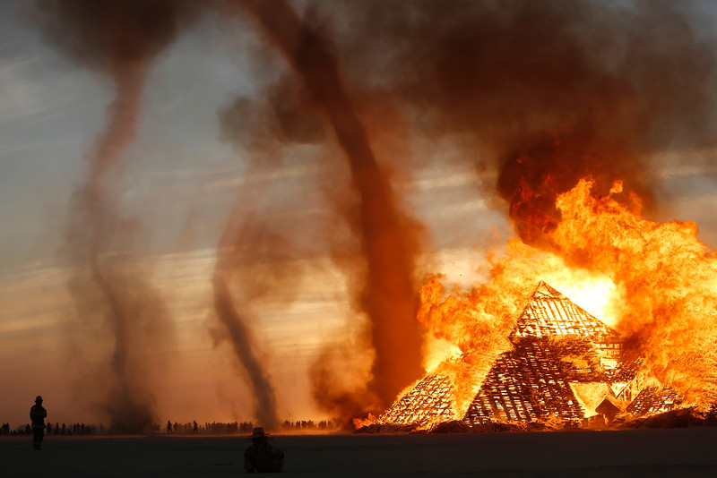 Firefighters monitor an art structure as it burns on the playa during the annual Burning Man festival in Black Rock Desert, Nev. on Sept. 1, 2016.