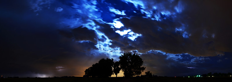 Once the storm clouds started to break, the moon came out.  <br /> <br /> This is a 3 shot panorama. You can still see some remaining lightning in the lower left, and the orange light behind the trees is light pollution from Denver.
