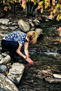 Woman washing the blood off her wrists in the stream