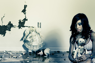 Beautiful girl sits in abandoned room with her burnt doll