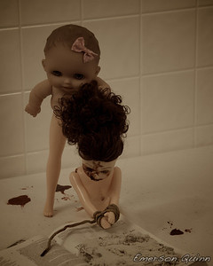 Bloody and beaten doll with wrists bound is foced to pray by the evil baby doll with long legs
