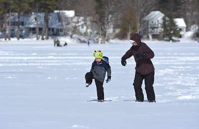 RYAN HUTTON/ Staff photo.  Beverly Kley and her grandson Matthew Occhinto, 5, trek across the frozen surface of Beaver Lake to check out different ice fishing spots as part of the Derry Frost Festival.