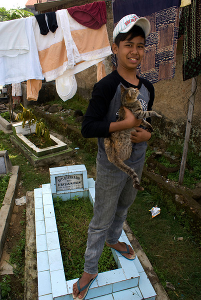 BOGOR. JAVA. JAVANESE BOY WITH A CAT ON THE GRAVE.