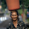 BALINESE LADY. CARRYING A PLASTIC BASKET. BALI. INDONESIA.