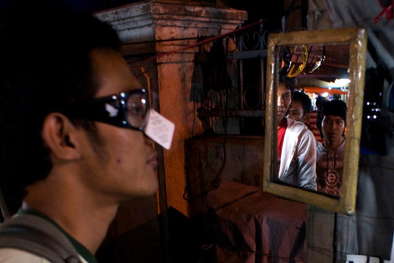 TESTING SUNGLASSES AT THE NIGHT MARKET. KOTA. JAKARTA. JAVA.