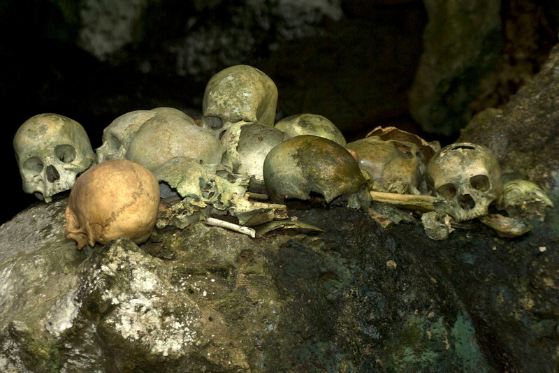 SKULLS ON A ROCK IN A CAVE (GRAVE). RANTEPAO. TANA TORAJA. SULAWESI.
