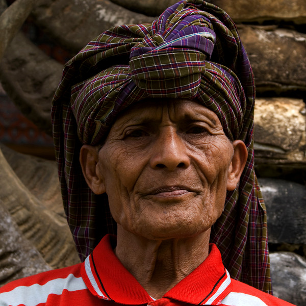 OLD MAN IN FRONT OF THE HORNS OF WATER BUFFALOES. TANA TORAJA. SULAWESI. INDONESIA.