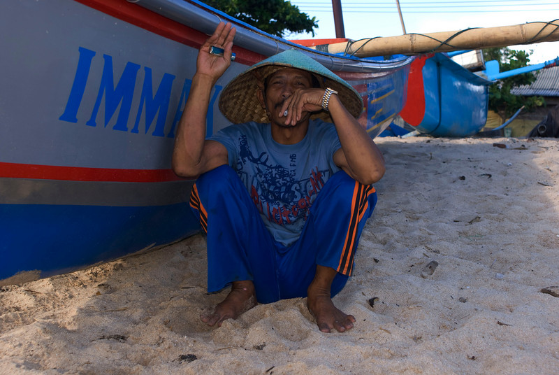 FISHERMAN SMOKING. BEACH OF KEDONGANAN. JIMBARAN BAY. BALI. INDONESIA.