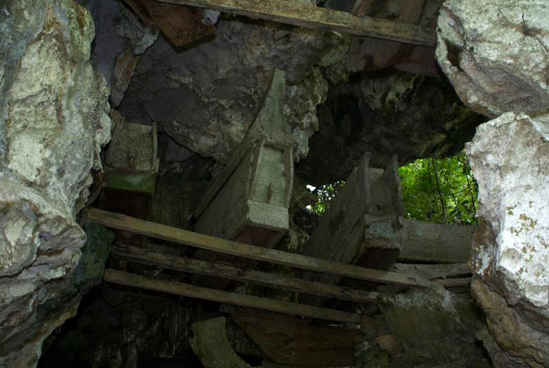 SULAWESI. TANA TORAJA. WOODEN COFFINS PERCH ATOP RICKETY SCAFFOLDING. CAVE GRAVE.