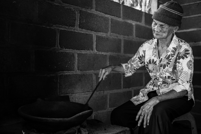 BALI. OLD LADY IS ROASTING COFFEE BEANS.