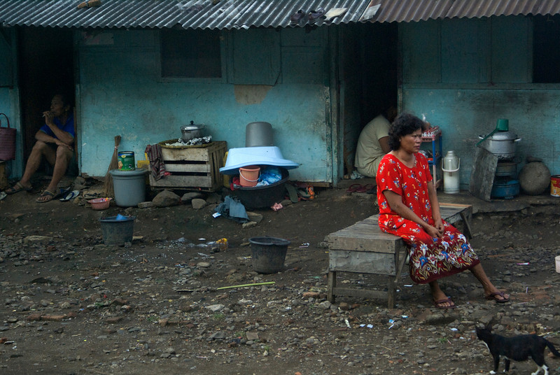 LADY IN RED WITH BLACK CAT. SLUMS OUTSIDE JAKARTA. JAVA. INDONESIA.