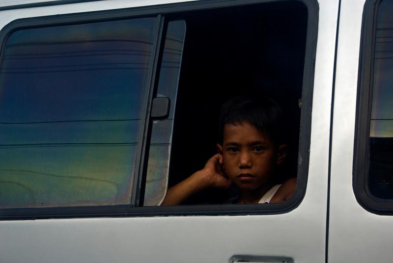 JAVA. BOY WAITING IN TRAFFIC JAM IN SURABAYA.