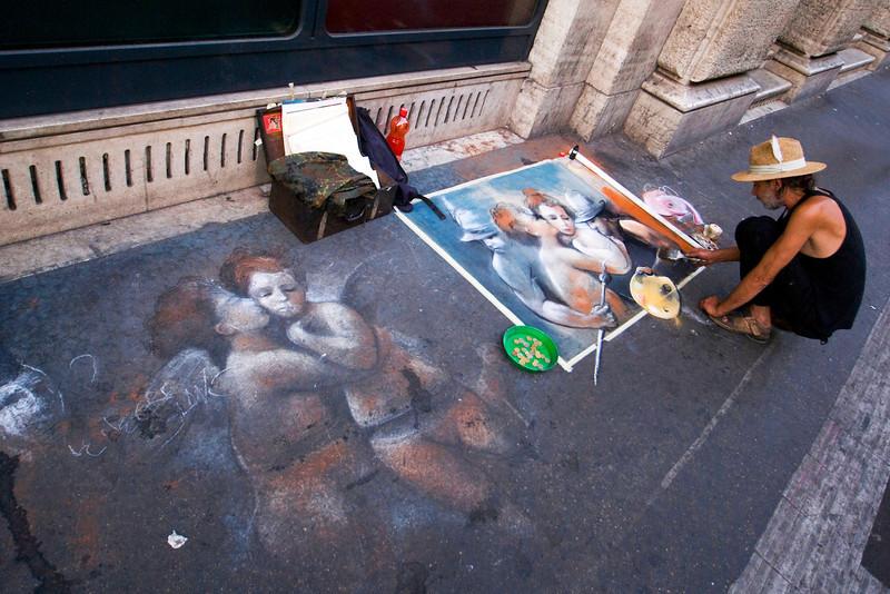 ROME. STREET ARTIST PAINTS ANGELS ON THE STREET.