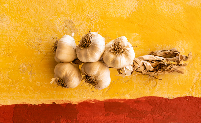 Fresh garlic hanging on a yellow wall in Puglia, Southern Italy