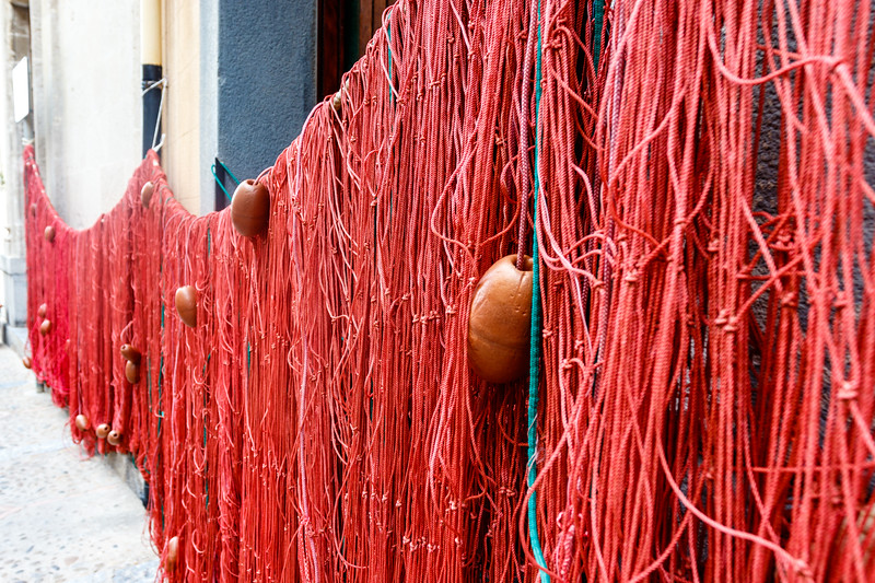 Red feshing nets drying in a street in Cefaly, Sicily, Italy