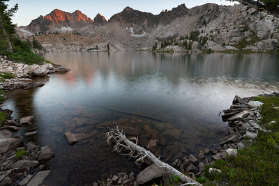 Wilderness, Sawtooth Mountains - Idaho  The Sawtooth National Wilderness Area has been my local mountain range for all of my life. There is probably enough of my blood in the rocks for it to be a relative. Years of climbing, backpacking, trail running, hiking, and exploring - and I still discover magical new lakes and cirques. This is Kathryn Lake, hardly an unknown, but just difficult enough to approach that only a handful of backpackers  reach its rocky shores each year. I love these high alpine lakes; no real flat ground, solid rock scored and polished by ancient glaciers, tiny wildflowers springing up in desperation wherever they can, cold lakes with small fish, sudden storms, scree fields the size of a city block, wise old trees dreaming of winter avalanches, big open skies - and pink and grey granite as far as you can see.