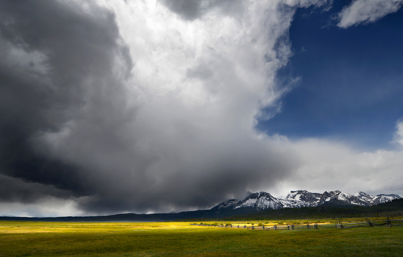 Spring Storm, Stanley - Idaho<br /> <br /> A spring storm races across Williams and Thompson peaks in the Sawtooth Wilderness Area. The criss-cross fences and open meadows of grasses and flowers are hallmarks of this scenic byway.