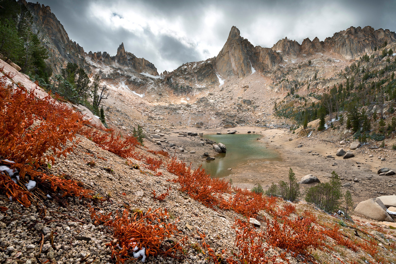 The Rotten Monolith, Sawtooth Mountains - Idaho<br /> <br /> Not far from Redfish Lodge, in the Sawtooth Wilderness Area, is a small cove of lakes - walled in by massive flanks of granite. Only a tiny slot near a cascade gives access to this area - where crossing beaver swamps, climbing over hundreds of downed trees, scrambling through a twisting labyrinth of loose stones and gravel, all lead to this image point. <br /> Here, in the early fall, the ground cover has turned crimson and the snow falls lightly throughout the day. The Rotten Monolith is seldom climbed from this side, and the first ascensionists actually reported placing pitons right into the rock by hand - without a crack!