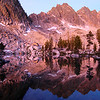 Lucille Lake, Sawtooth Mountains - Idaho<br /> <br /> Lucille Lake, high in the Sawtooth Mountains of Idaho, is a seldom visited rocky cirque of cold deep lakes, treed granite islands, and spectacular sunrises. On this particular morning, the sun's rays poured light through a layer of forest fire smoke that had filled the Stanley Basin in the evening. The resulting color that was cast on the mountains was quite unnatural - but beautiful nonetheless.