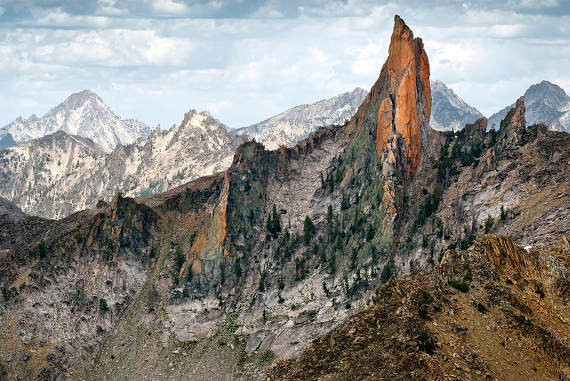 The North Raker, Sawtooth Mountains - Idaho<br /> <br /> The North Raker, a sabertooth of orange granite, pierces the skyline of the Sawtooths, and can been seen from almost any high point in the range. It is indeed remote, and no trail comes close to its flanks and ring of small alpine lakes at its base.  The peak was named, with its twin sister summit, the South Raker, for their resemblance to the teeth of a cross-cut saw. Seldom climbed, as it is still graded a 6.0, the North Raker has probably only been summited a handful of times since its first ascent in 1949 by the indomitable Fred Beckey.