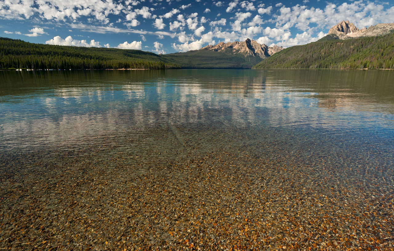 Redfish Lake, Stanley - Idaho<br /> <br /> From the shallow end of Redfish Lake, small water-washed pebbles sparkle in the morning sunshine. This shallow beach reaches far into the lake before dropping into the cold blue depths. Mt. Heyburn and the Grand Mogul, at the far end of the lake, are iconic peaks of the Sawtooth National Recreation Area. Redfish Lodge, and the Redfish Visitor Center are located here, offering boat shuttles for backpackers, hotel rooms for guests, a restaurant offering up fresh trout, and an interpretive center leading day hikes and selling local artwork.