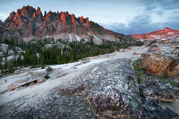 Crimson Dragon, Sawtooth Mountains - Idaho  Evening light paints the granite spires of the Monte Verita complex with a crimson glow,  like the serrated spines of a great dragon.  This image was taken at Feather Lakes, just at the foot of Warbonnet Peak.