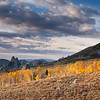 October Morning, City of Rocks - Idaho<br /> <br /> Early light paints the aspen groves with brilliant color, as rain clouds drift toward the horizon - over the twin summits of the Twin Sisters. For many years, pioneer wagon trains followed the meandering ruts of the California Trail, through the towering rock spires of the City of Rocks, in route to the mythical goldfields that awaited them along the Pacific coast.