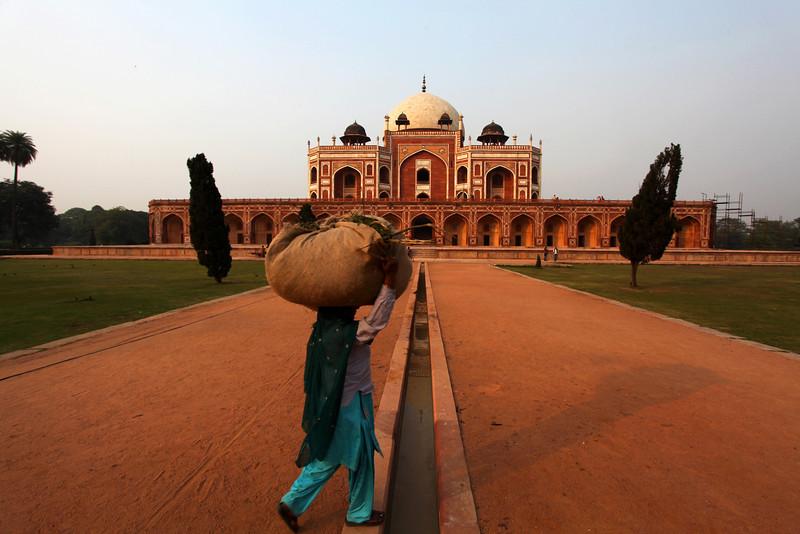 DELHI. HUMAYUN'S TOMB. CARRYING GOODS AT SUNSET.
