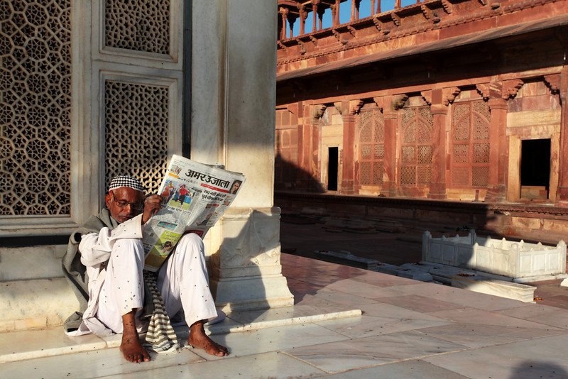 FATEHPUR SIKRI. JAMA MASJID. READING THE NEWSPAPER. UTTAR PRADESH. INDIA.