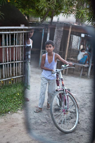 ASSAM. BOY WITH HIS BIKE ON THE STREET.