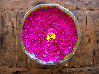 Centerpiece, Flores Island - Indonesia  Painstakingly hand placed flower petals in an offering bowl. Reclaimed teak wood produces the tabletop.