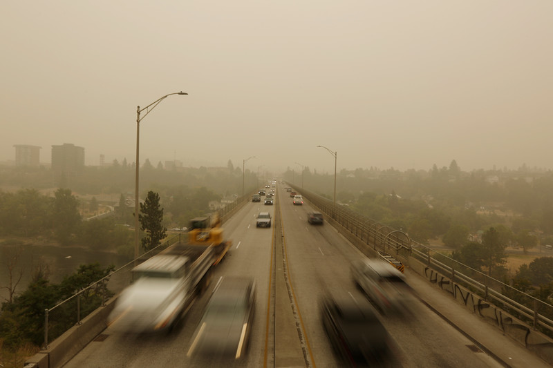 in this slow shutter photograph, vehicles travel the Maple Street Bridge as seen from the Centennial Trail in the Kendall Yards neighborhood of Spokane, Wash., as smoke from wildfires in Washington, Oregon and California covers the region, Monday, Sept. 14, 2020. The smoke resulted in hazardous air quality in the area per the Spokane Regional Clean Air Agency. (Young Kwak)