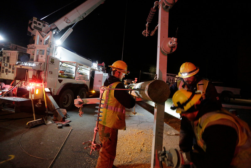 Avista Utilities Apprentice Lineworker Nate Thurston, left, Journeyman Lineworker Taylor Jacobs, center, and Journeyman Lineworker Willy Harris attach dead ends to a utility pole near the corner of E. 17th Ave. and S. Mt. Vernon St., Friday, Nov. 20, 2015, in Spokane, Wash. A major windstorm on Tuesday, Nov. 17 knocked out power to a majority of customers in Spokane and surrounding areas. (Young Kwak/Pacific Northwest Inlander)