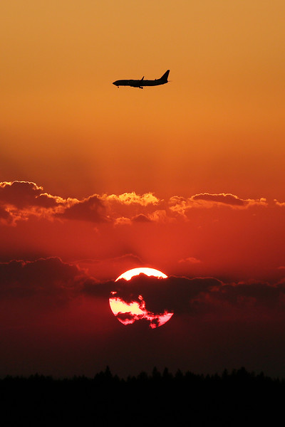 An airplane approaches Spokane International Airport as smoke from the Andrus Fire near Cheney, Wash., creates a warm hued sunset as seen from S. High Dr. near W. 29th Ave., Monday, July 5, 2021, in Spokane, Wash. (Young Kwak)