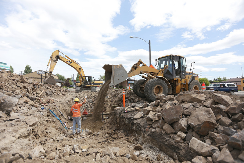 MDM Construction employee Warren Anglin, left, guides a front loader dropping bedding, driven by fellow employee Cayle Steven during a City of Spokane, Wash., water pipe replacement project on E. 3rd Ave., between S. Division St. and S. Arthur St., on Friday, June 7, 2013. (Young Kwak/The Pacific Northwest Inlander)