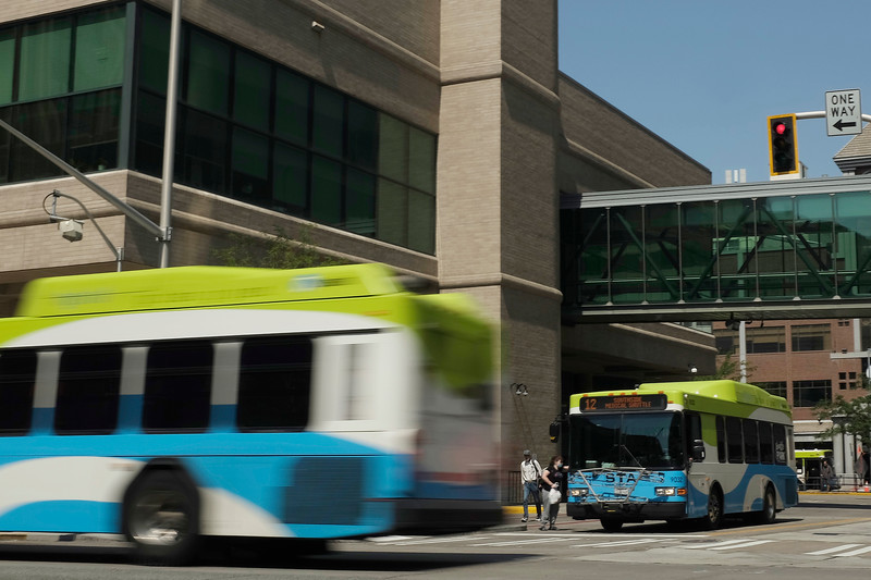 In this slow shutter photograph, a bus, left, approaches and another departs the Spokane Transit Authority Plaza, Monday, Aug. 9, 2021, in Spokane, Wash. (Young Kwak)
