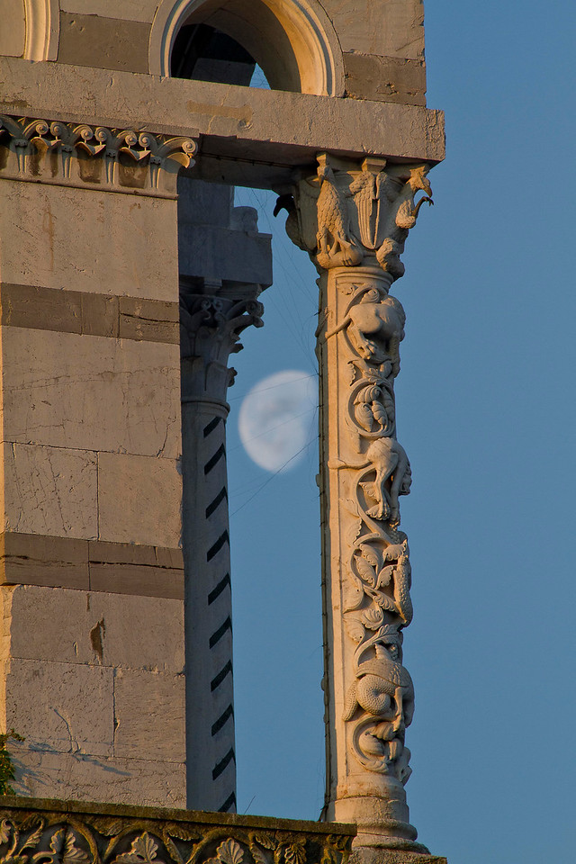 Moon behind church columns  in Lucca