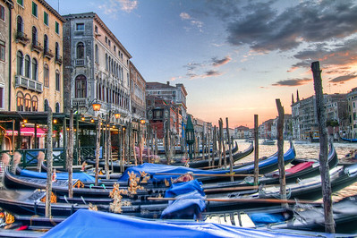 Sunset in Venice, Italy on the Grand Canal  One the most unique and romantic cities in the world, Venice,Italy. This photograph is looking west as the sun sets over the Grand Canal with a great view of the classical Venetian boat, the gondola. As you can see, the gondolas are docked in the harbor showing their ornate appearance for tourists. The hotels and restaurants are beginning to light up for the evening. Just behind me is the Ponte di Rialto (the oldest bridge across the canal).  I took this photograph on a typical April night. What wasn't typical was getting lost on my way back to my hotel for an hour and a half! But I learned a lesson. Always remember what Piazza your hotel is located in because street addresses on maps are worthless