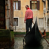 Venice goldolier in a narrow canal, low tide