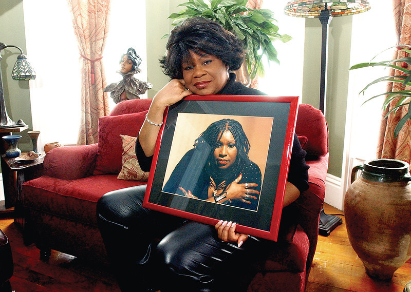 Connie Fredericks-Malone of Canandaigua holds a photograph of her  late sister Carole Fredericks in her living room.