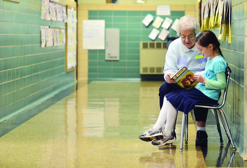 "JACK HALEY/MESSENGER POST<br /> First grader Amberly Rowden reads to Lucille Cali in the hallway at Indian Landing Elementary School. Cali and other seniors participate in a program at the school called ""Grandpartners."""