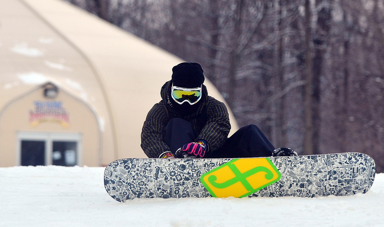 A snowboarder hooks in on top of Bristol Mountain before making a run.
