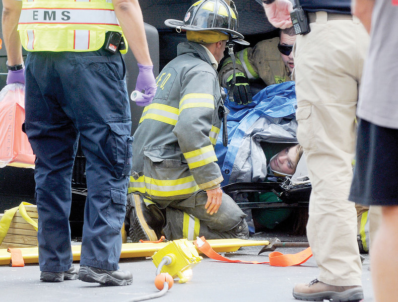 JACK HALEY/MESSENGER POST<br /> Canandaigua firefighters used a tarp to cover the victim who is smiling of the MVA at South Main Street and Chapin Street to protect her from glass and debris as they extracaited her from the vehicle which was on it's side.